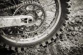 stock photo of motocross  - Rear wheel of sport bike on dirty motocross road - JPG