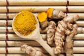 picture of rhizomes  - Ground turmeric on wooden spoon and rhizomes on bamboo mat - JPG