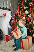 Little boy sits on big cardboard gift box, holding another in his hands near decorated Christmas tre