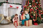 Little boy sits on big cardboard gift box, holding another one in his hands near decorated Christmas