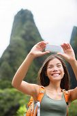 Woman hiker taking selfie photo using smartphone while hiking on Hawaii enjoying outdoor activity. W
