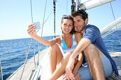 Couple on sailboat taking picture with smartphone