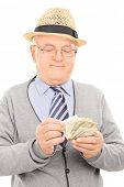 Male pensioner counting money isolated on white background