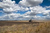 image of plowing  - Tractor plowing field deep blue sky Summer clouds San Joaquin Valley California - JPG