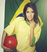 Beautiful young woman wearing Brazil soccer colors holding football