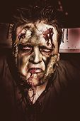 image of gash  - Dark halloween portrait of a scary zombie with blood gashing from monster mouth and carving knife in head - JPG