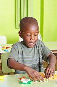Happy african child playing in kindergarten with building blocks