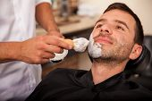foto of shaving  - Closeup of a barber putting some shaving cream on a client - JPG