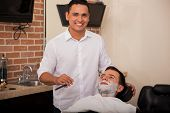 stock photo of barber razor  - Portrait of a handsome young barber holding a razor and about to shave a man - JPG