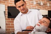 stock photo of barber razor  - Young Hispanic barber doing his work and shaving a client - JPG