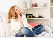 Smiling happy woman sitting on sofa and using tablet
