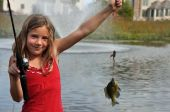 stock photo of catching fish  - a young girl catches her firest fish - JPG