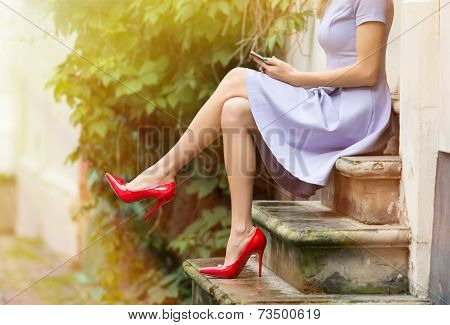 Fashionable woman sitting on stairs and using mobile phone