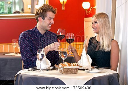 Young Couple Toasting Each Other With Red Wine