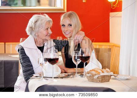 Old And Young Women At Table Having Snacks