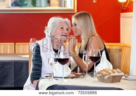 Old And Young Women Talking At Restaurant Table