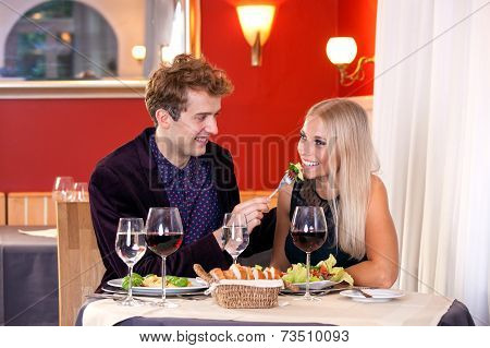 Pretty Smiling Young Lovers Date At Restaurant