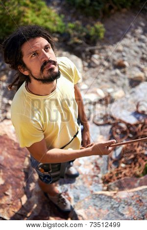 A man with dreadlocks holding on to a rope and looking up ready to climb up a mountain