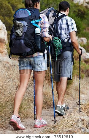 Fit couple with their backpacks on walking along a hiking path