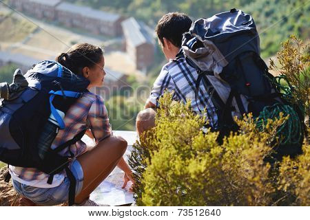 A young hiking couple crouching down and looking at a map