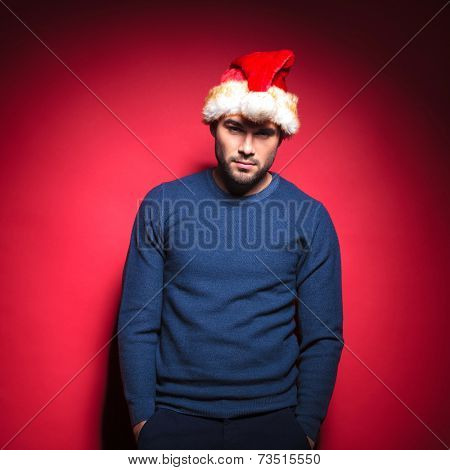 Sexy young man wearing a red santa hat holding his hands in pockets. Leaning on red background.