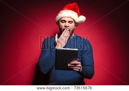 Tired santa man reading on a tablet pad computer while yawning. Against red background.