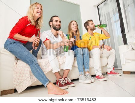 Group of friends at home watching a sport event on television