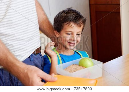 happy young boy with dad and healthy food apple in lunch box for school