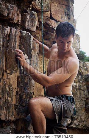 A topless man rock climbing with big muscles