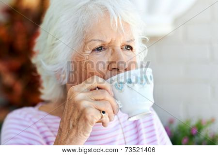 A senior woman taking a sip of her tea