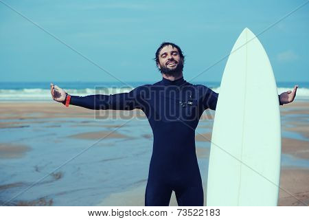 Young surfer feeling so happy, attractive surfer enjoying perfect sunny day standing on the beach