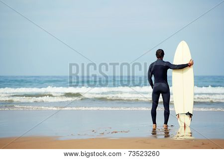 Surfer holding surfboard while standing on the beach and looking at ocean to find the perfect spot