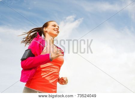 fitness, sport and lifestyle concept - smiling young woman with earphones running outdoors