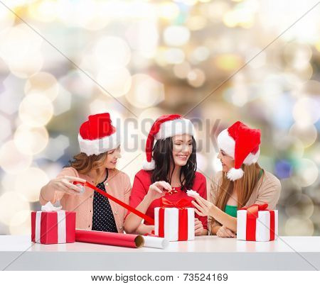 christmas, holidays, celebration, decoration and people concept - smiling women in santa helper hats with decorating paper and gift boxes over lights background