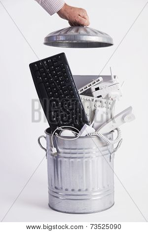 Businessman Filling Garbage Can With Obsolete Office Equipment
