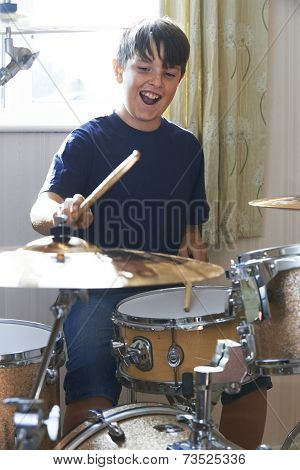 Boy Playing Drum Kit At Home