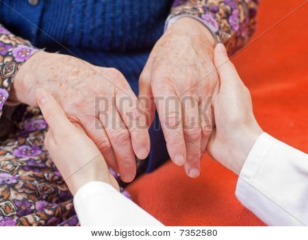 Young Sweet Doctor Holds The Old Woman's Hand