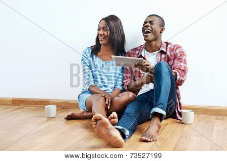 happy young african couple looking on tablet computer for new home furnishings for their apartment