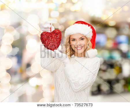 happiness, winter holidays, christmas and people concept - smiling young woman in santa helper hat with red heart decoration over lights background