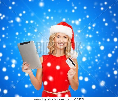 christmas, technology, shopping and people concept - smiling woman in santa helper hat with tablet pc computer and credit card over blue lights background