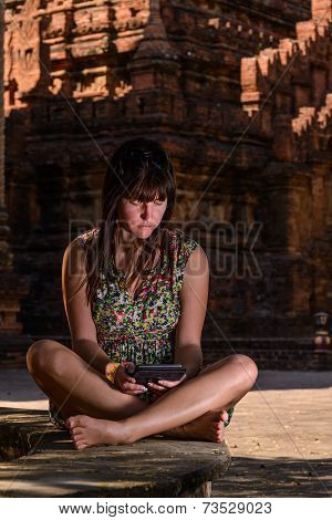 Woman Reading On Her Ebook Reader, Bagan, Myanmar