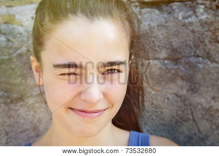 Portrait Of A Smiling Teenage Girl Squinting One Eye