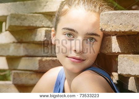 Portrait Of A Teenage Girl Leaning Against A Stack Of Flagstones