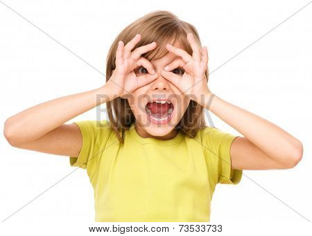 Happy little girl is showing glasses gesture, isolated over white