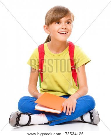 Portrait of a cute little schoolgirl with backpack reading her book, isolated over white