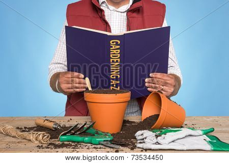 A gardener standing at a workbench reading a GARDENING A-Z book