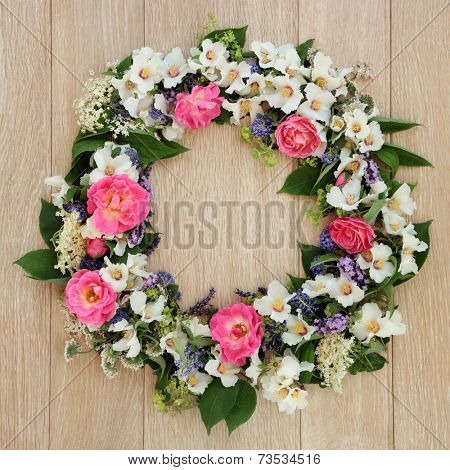 Summer flower wreath over light oak background.