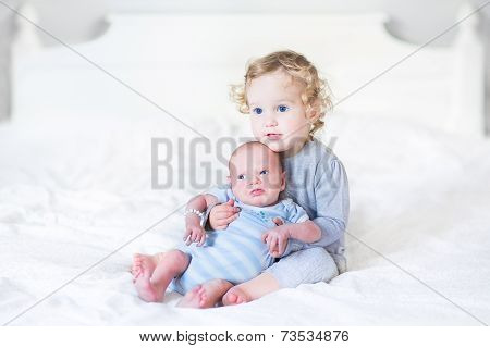 Beautiful Toddler Girl Holding Her Newborn Baby Brother On A White Bed
