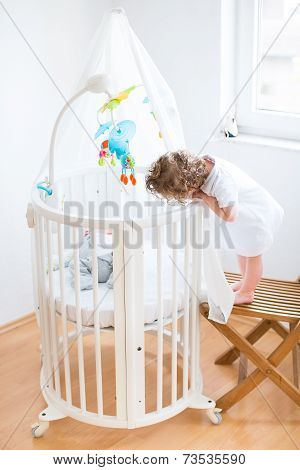 Funny Curly Toddler Girl Looking At Her Newborn Baby Brother In A White Round Bed With Canopy