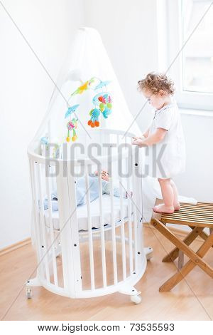 Cute Toddler Girl Standing On Chair And Watching Her Newborn Brother In A White Round Crib